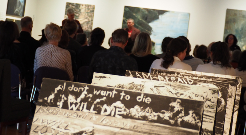 A group of seated people listen to a talk in the Art Gallery. Artworks are in the foreground and background
