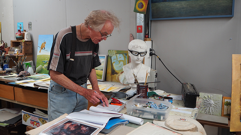 Artist Eric Brew in his studio, surrounded by books and art materials
