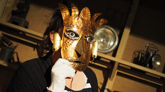 A woman wears a gold coloured metal mask in a Mexican style. Behind her are lamps and blacksmithing equipment