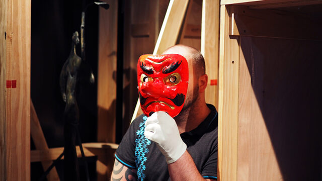 A man wears a bright red Japanese theatre mask in the sculpture store room