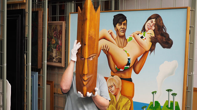 A woman wears a wooden Samoan mask in the art collection store. Behind her is a colourful painting of a man and woman in swimwear