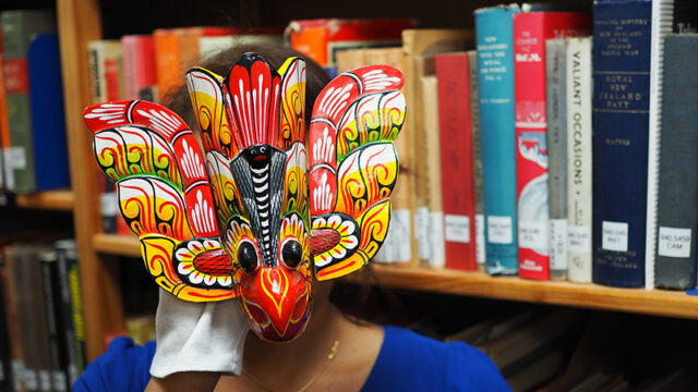 A woman wears a brightly coloured Sri Lankan bird mask in a library