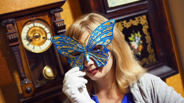 A woman wears a blue and gold Venetian carnival mask. Behind her on the wall are old clocks.