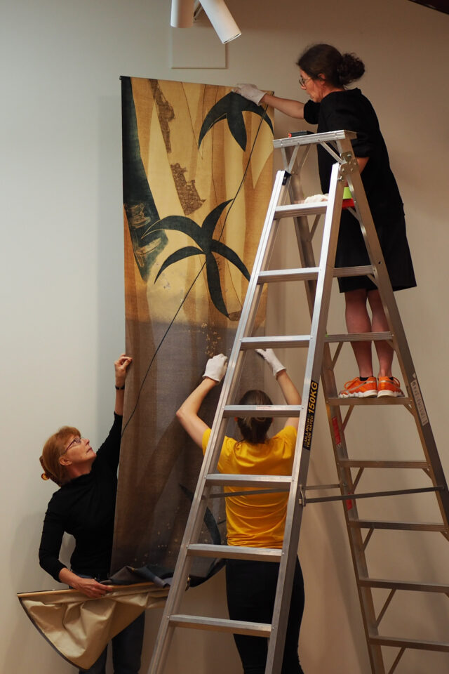 Three women hang a giant printed panel in the Te Manawa Art Gallery